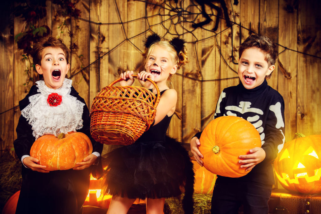 Two boys and a girl in Halloween costumes while holding pumpkins and a basket
