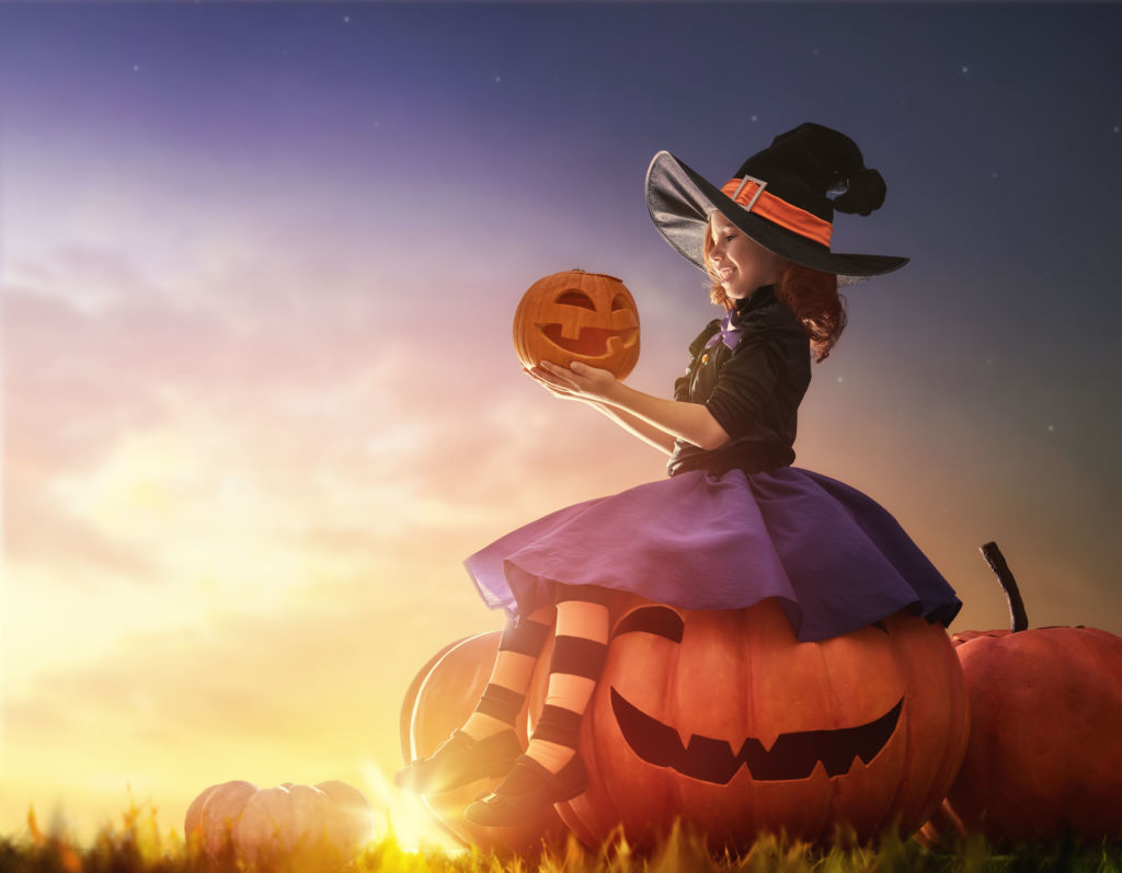A young girl sits on a large pumpkin while holding a small pumpkin.