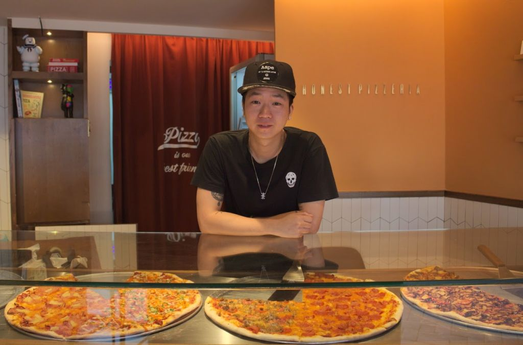 Co-owner of Honest Pizzeria, Tik, posing at the front counter display of pizzas at Honest Pizzeria in Taipa Macau