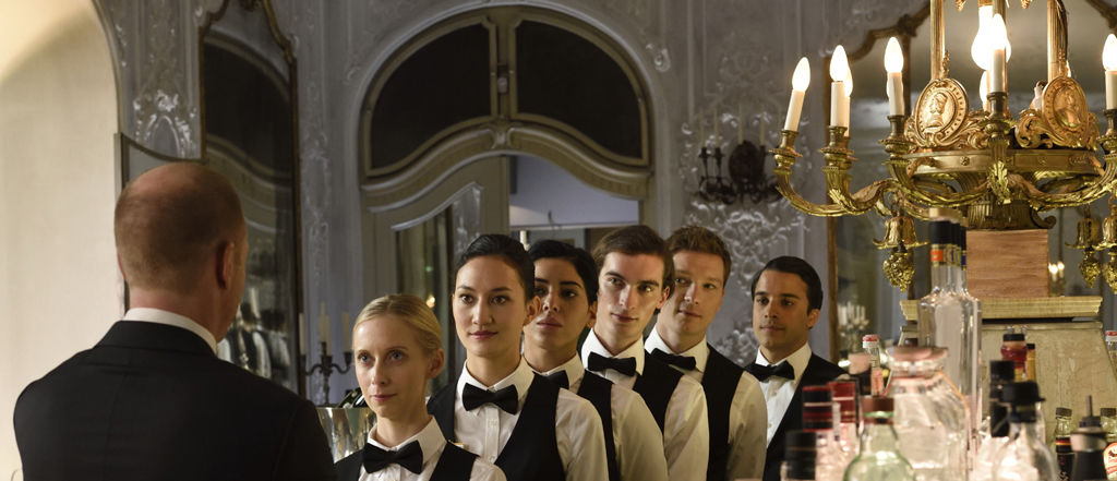 A scene from a German movie showing waitstaff lined up and listening to a man speaking