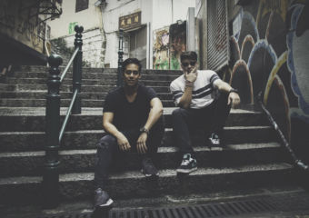 Two young men sitting on steps on a small street in Macau