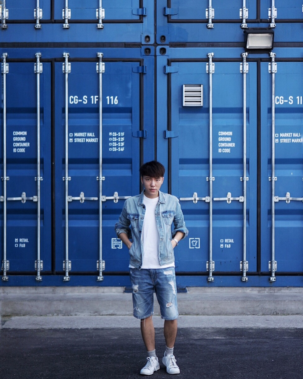 A young man wearing a denim jacket, white t-shirt, and denim shorts poses in front of a blue background in Macau.