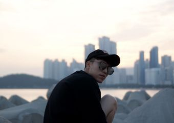 A young man wearing a dark hat and sunglasses sits on a rock with the Macau cityscape in the background.