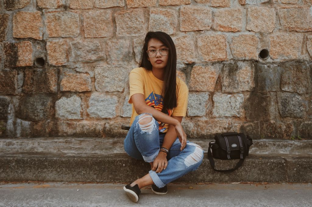 A young woman poses on the street wearing a yellow t-shirt and jeans