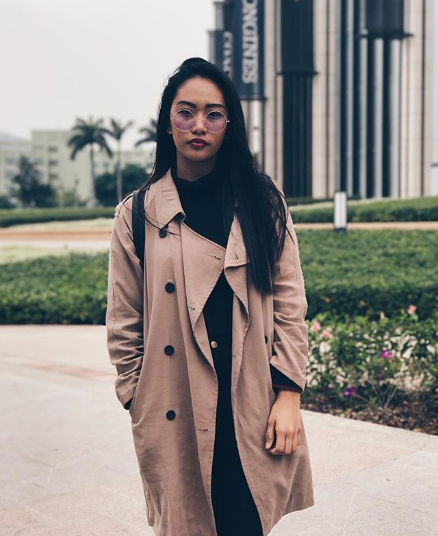 A young woman poses standing outside in Macau, wearing large wire-rimmed glasses and a long light brown overcoat.