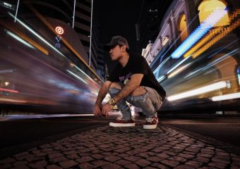 A young man wearing a hat and jeans kneels on the street in Macau