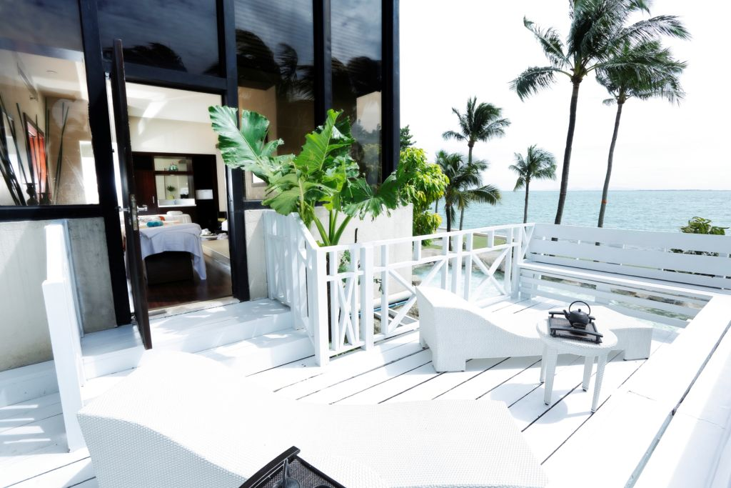 A beachside veranda painted white with matching white deck furniture. Palm trees in the background and distance.