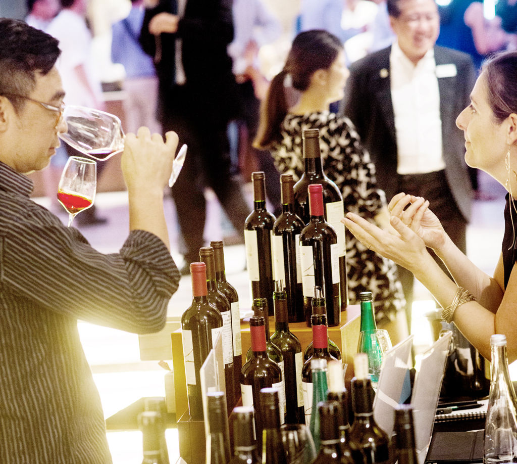 A man and a woman taste wine and while discussing the wine.