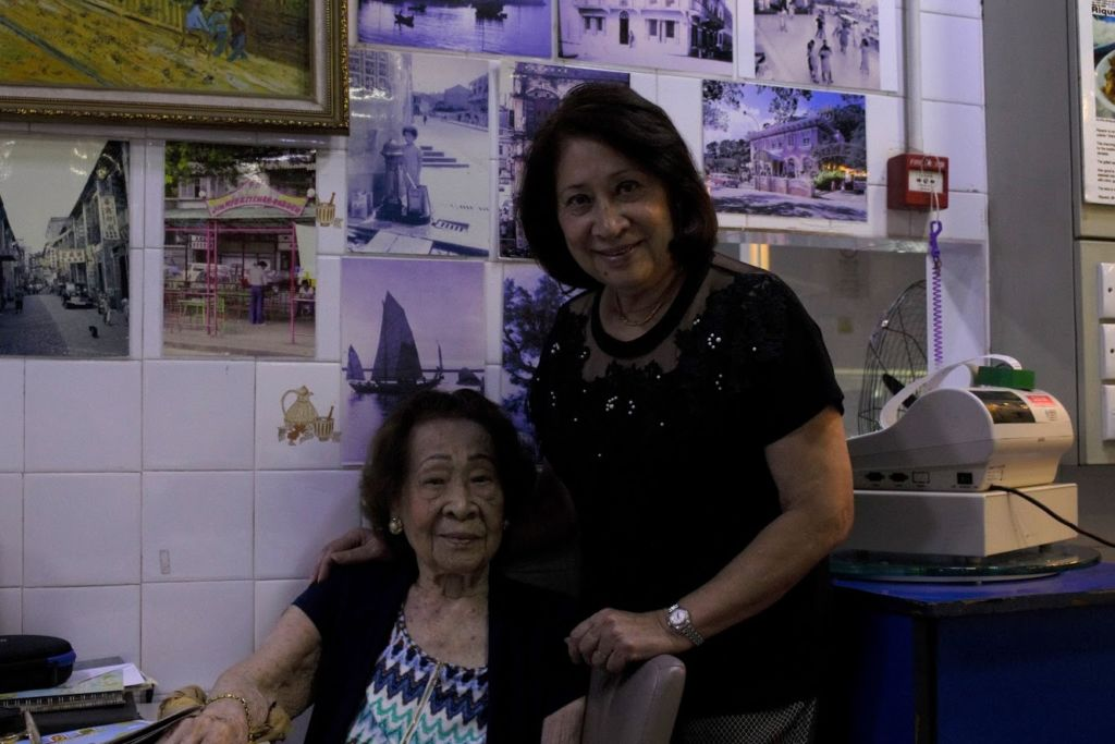 Two older women pose at a restaurant.