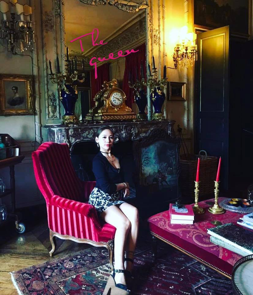 A woman wearing a skirt sits in a red upholstered living room chair.