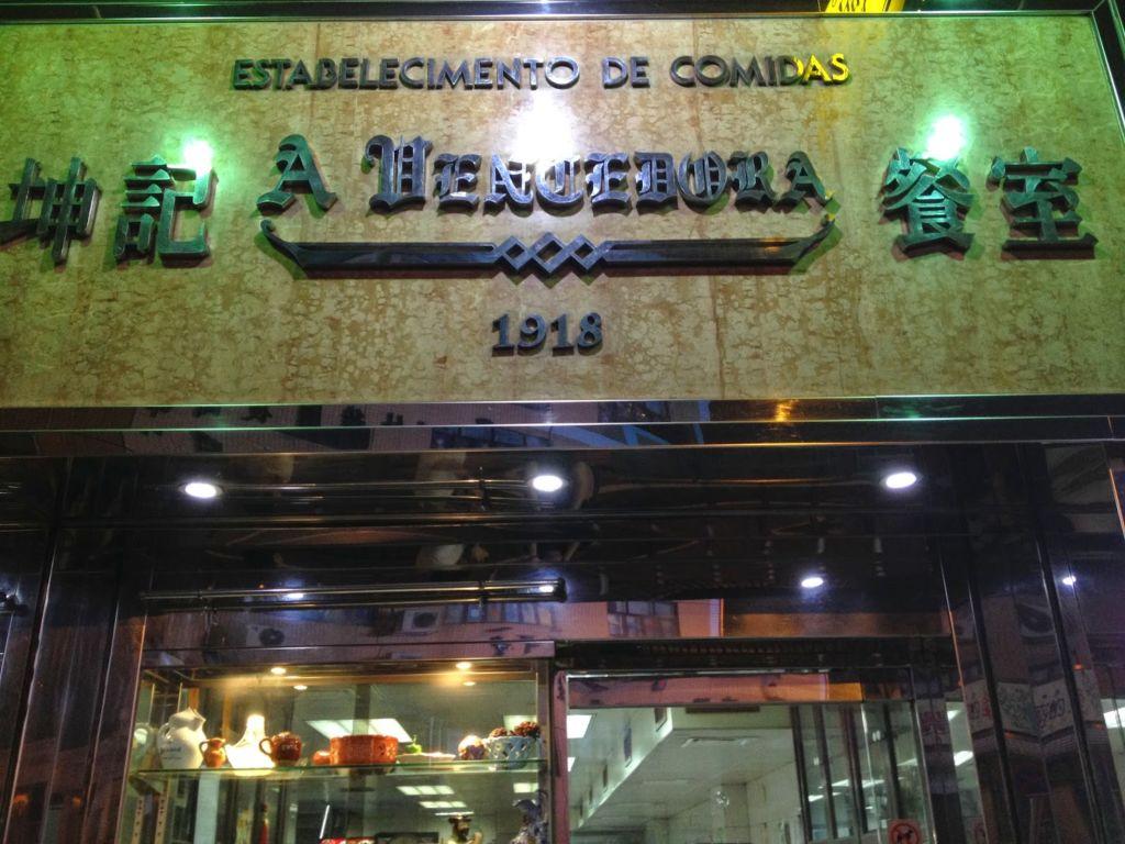 The exterior sign for A Vencedora restaurant in Macau