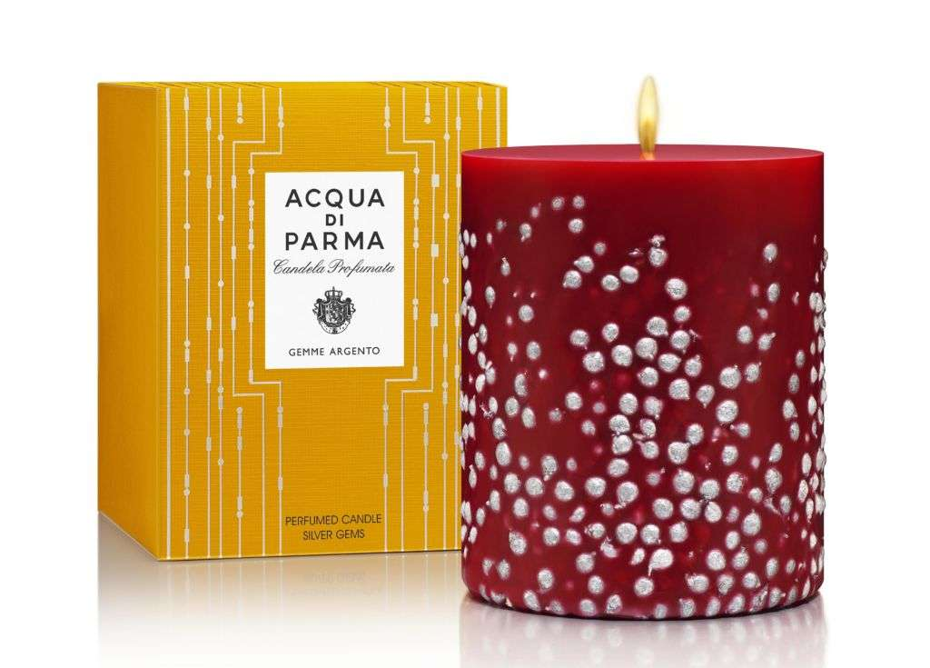 A red and white candle from Acqua di Parma with its yellow box in the close background