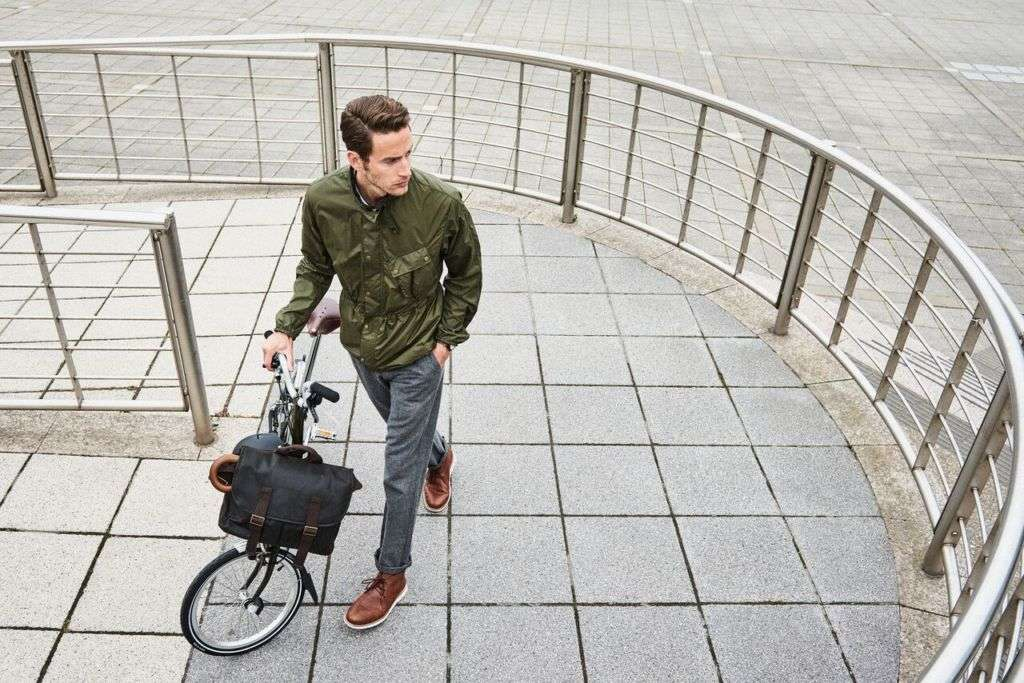 A man with a folding bicycle standing on the street.