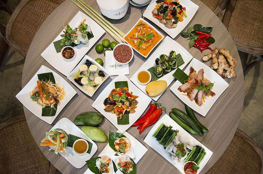 A large selection of Thai dishes arranged on a table and viewed from above.