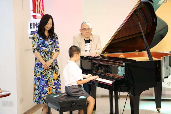 A boy playing piano while a woman and man watch