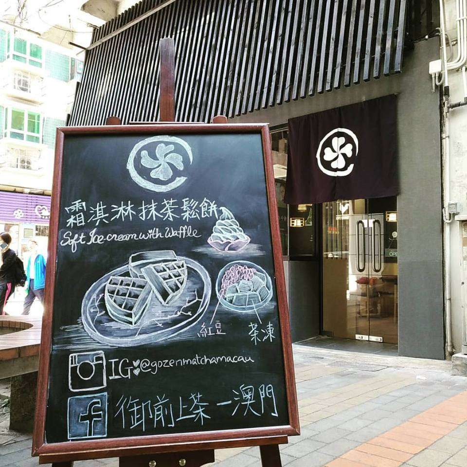 A chalkboard advertising restaurant on the street in Macau.