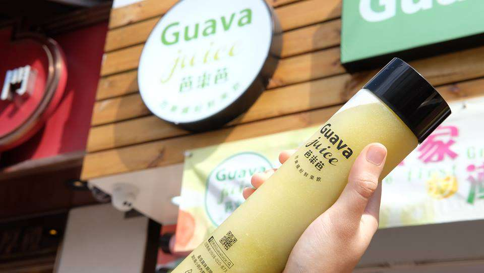 Someone holding a bottle of juice from a Guava Juice cafe in Macau.