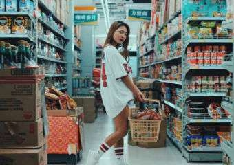 A young woman poses in a supermarket, holding a shopping basket.