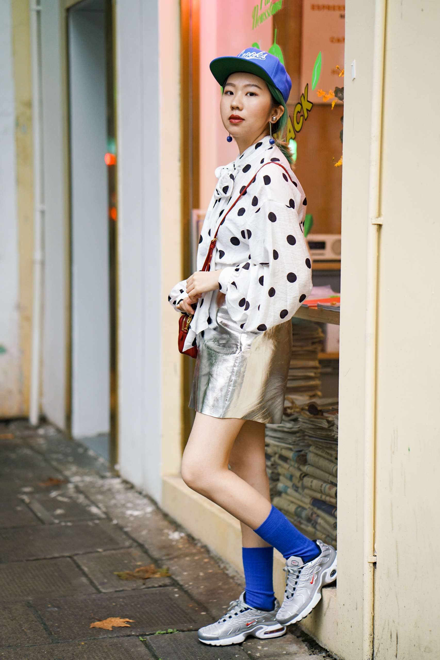 A young woman poses on the street wearing a blue cap, polka dotted shirt, and blue socks.