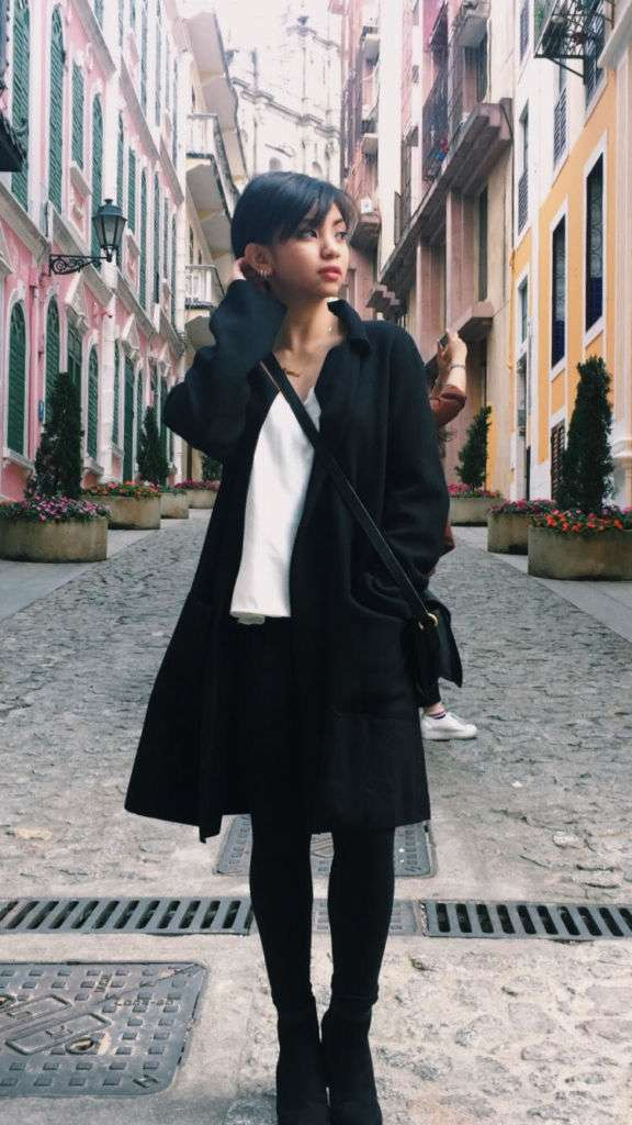 A young woman stands on a Macau street wearing a dark overcoat and white top.