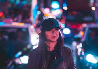 A young woman on the street at night wearing a baseball cap and dark outfit.