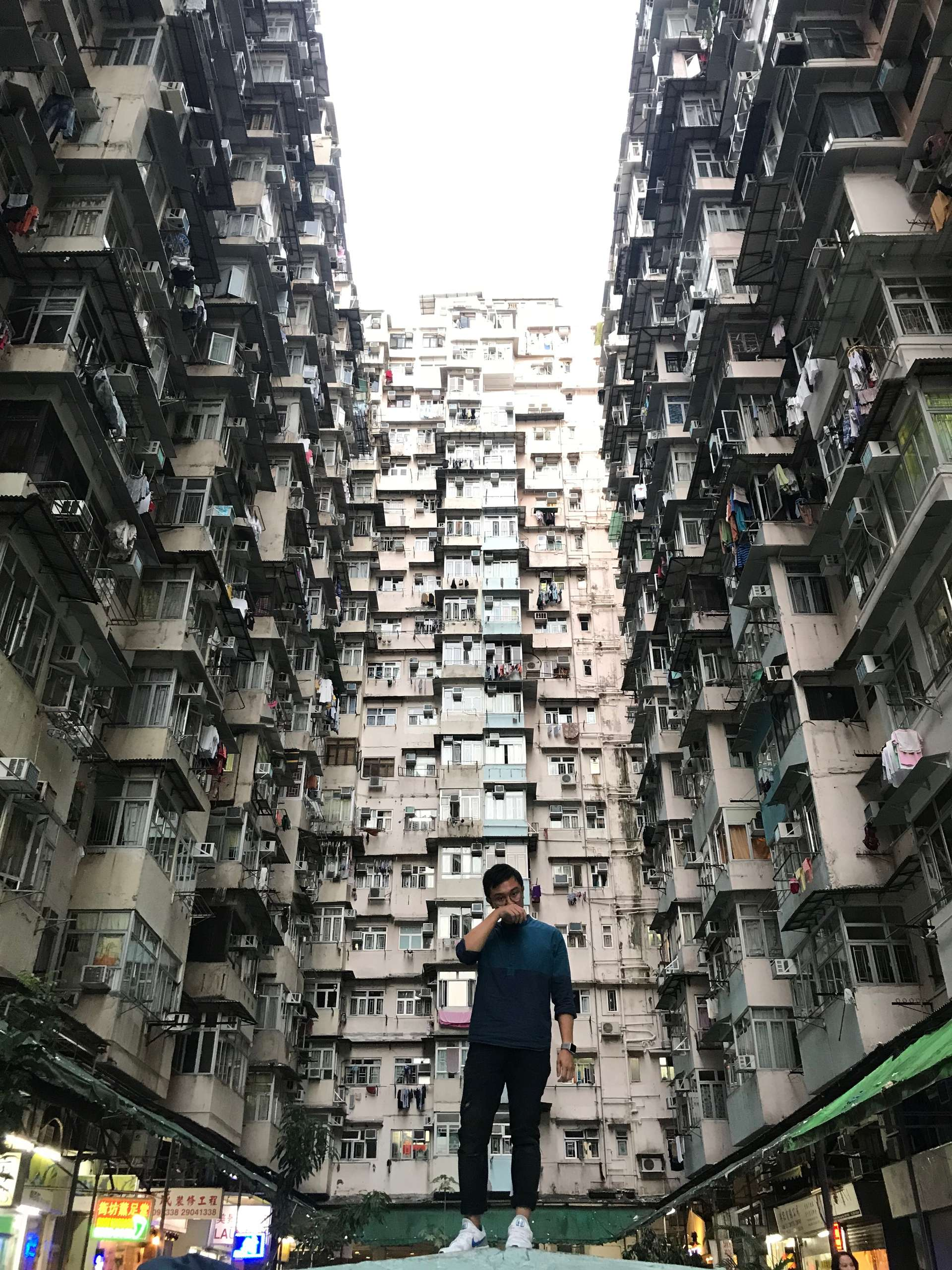A young man posing with high residential blocks in background in Macau.