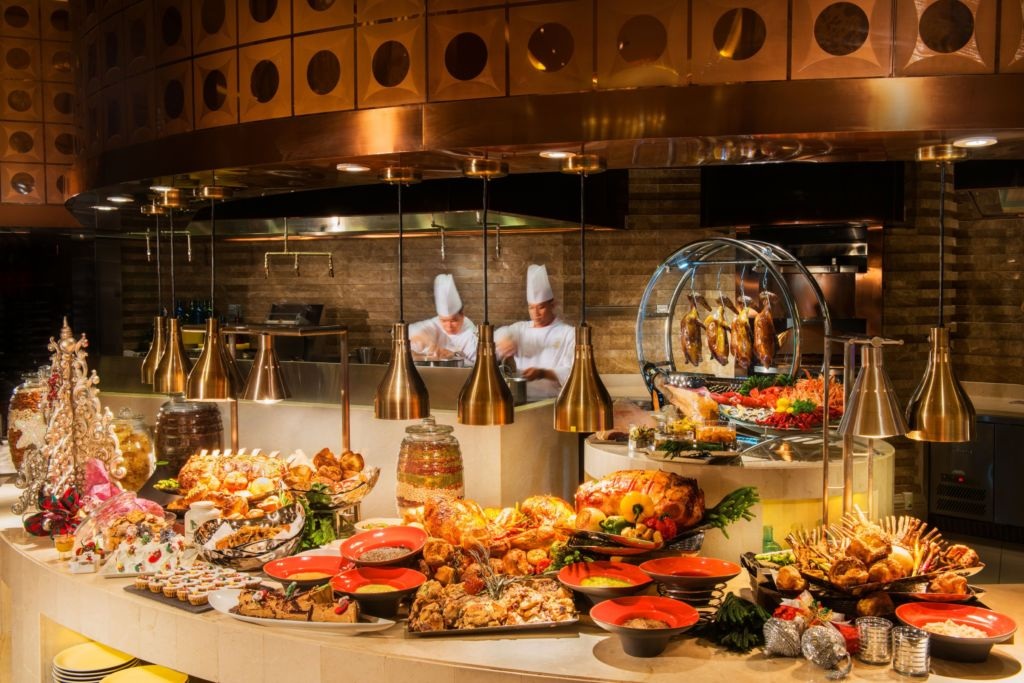 Two chefs working at a buffet.