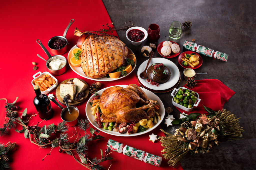 Roast turkey and pork shoulder displayed on a table with small side dishes.