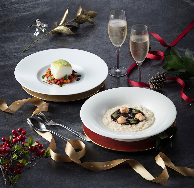 Seafood risotto and another seafood dish displayed against a grey backdrop with Christmas decorations.