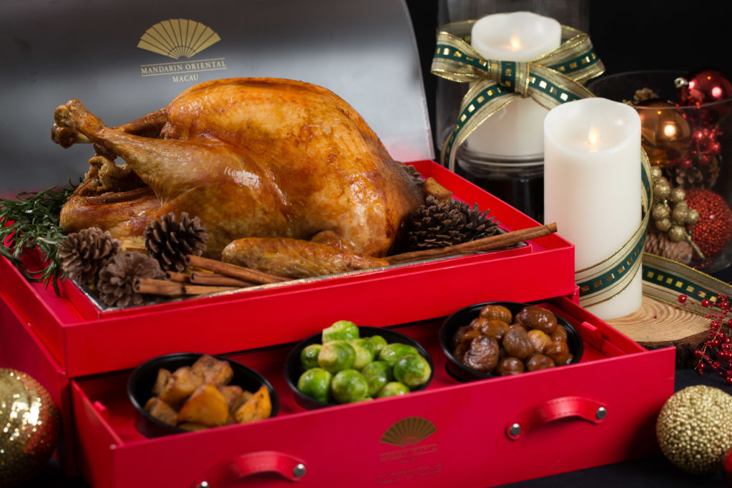 A roasted turkey with side dishes served in a red box with drawers.