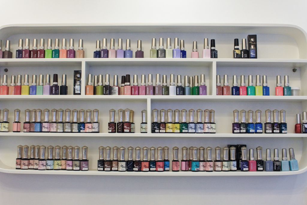 4 levels of shelves displaying various nail polishes and other nail-related supplies.