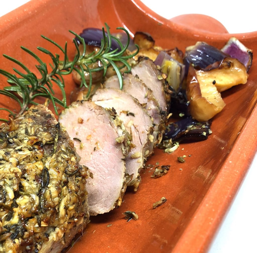 A roasted pork loin sliced on a wooden serving tray.