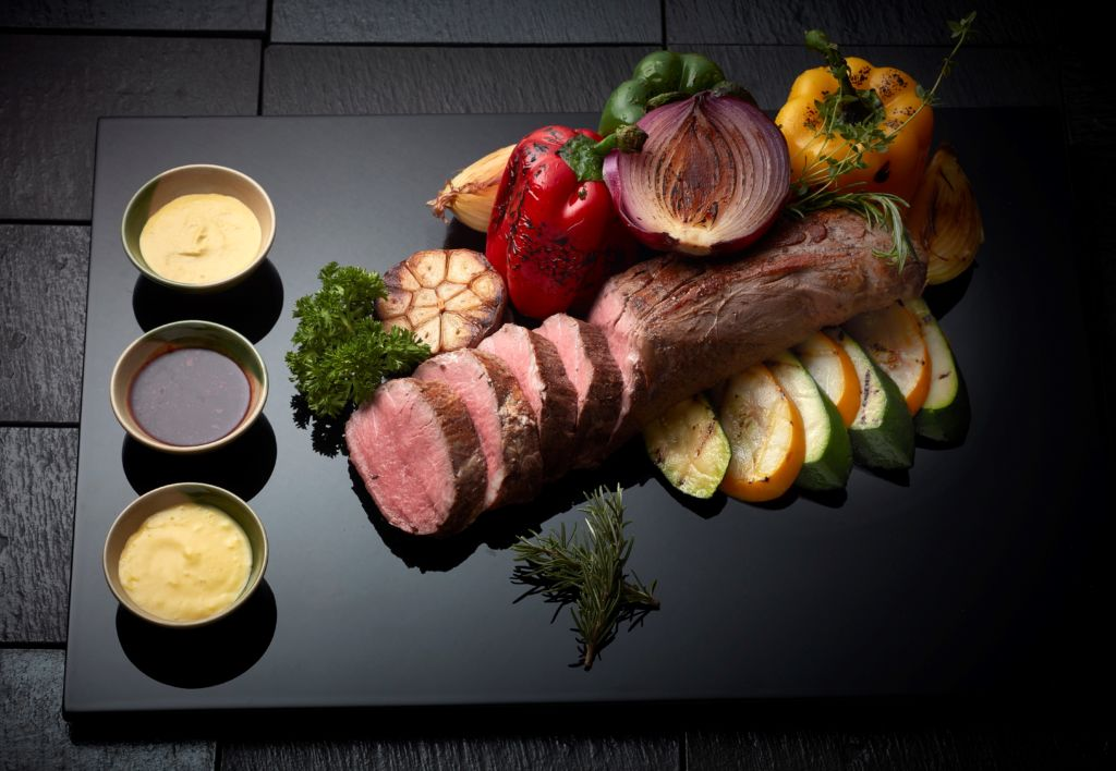 A beautiful cut of pork sliced and served on a black lacquer presentation tray.