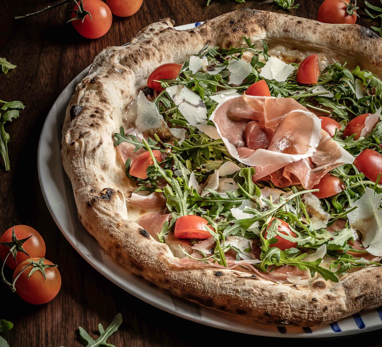 CasaDonAlfonso Pizza with mozzarella Parma ham wild arugula cherry tomatoes parmesan flakes and aged Modena balsamic vinegar