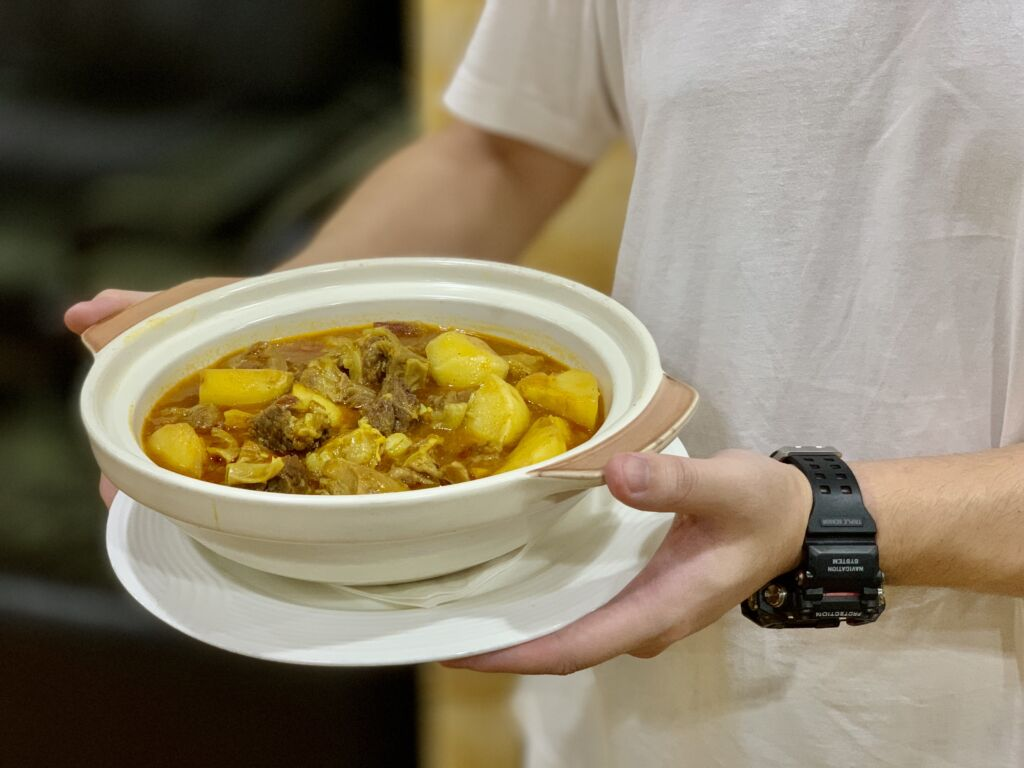 Julio Lei holding a pot of ox tail curry from APOMAC Macau Lifestyle
