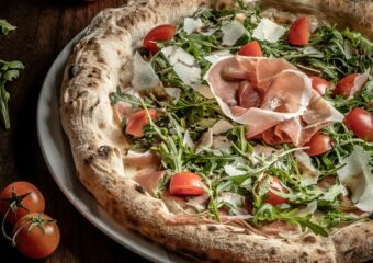 Pizza Ricca_(Pizza with mozzarella, Parma ham, arugula, cherry tomatoes, parmesan flake and balsamic vinegar)