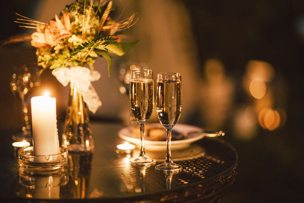 Two glasses of wine on table on the background of wedding bouque